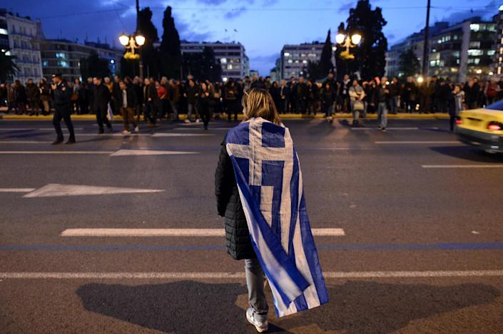 A woman wrapped in a greek flag makes her way in front of the Greek parliament in Athens on February 5, 2015 as people gather in support of the new anti-austerity government's efforts to renegotiate Greece's international loans (AFP Photo/Louisa Gouliamaki)