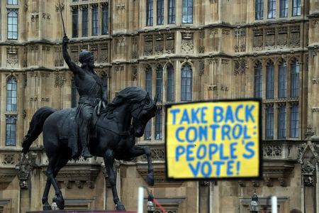 FILE PHOTO: An Anti-Brexit sign is seen next to a statue of King Richard I outside the Houses of Parliament, in Westminster, London, Britain March 4, 2019. REUTERS/Hannah McKay/File Photo