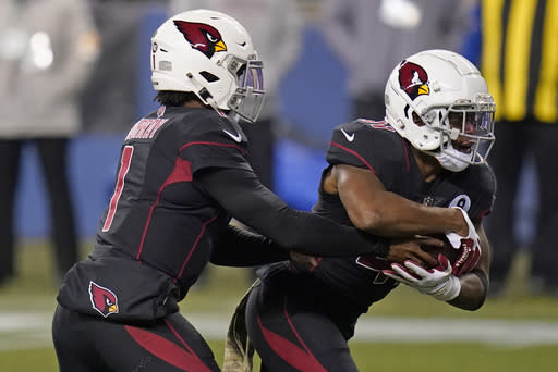 Arizona Cardinals quarterback Kyler Murray, left, hands off to running back Kenyan Drake, right, during the first half of an NFL football game against the Seattle Seahawks, Thursday, Nov. 19, 2020, in Seattle. (AP Photo/Elaine Thompson)