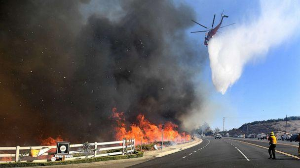 PHOTO: A water-dropping helicopter passes makes a drop along Madera Road as the Easy Fire burns in Simi Valley, Calif., Oct. 30, 2019. (Wally Skalij/Los Angeles Times/Polaris)