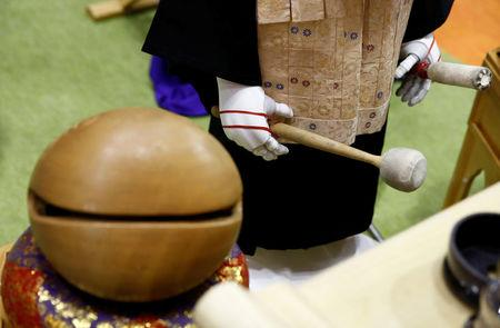 A 'robot priest' wearing a Buddhist robe holds a stick to beat a wooden fish during its demonstration at Life Ending Industry EXPO 2017 in Tokyo, Japan August 23, 2017. REUTERS/Kim Kyung-Hoon