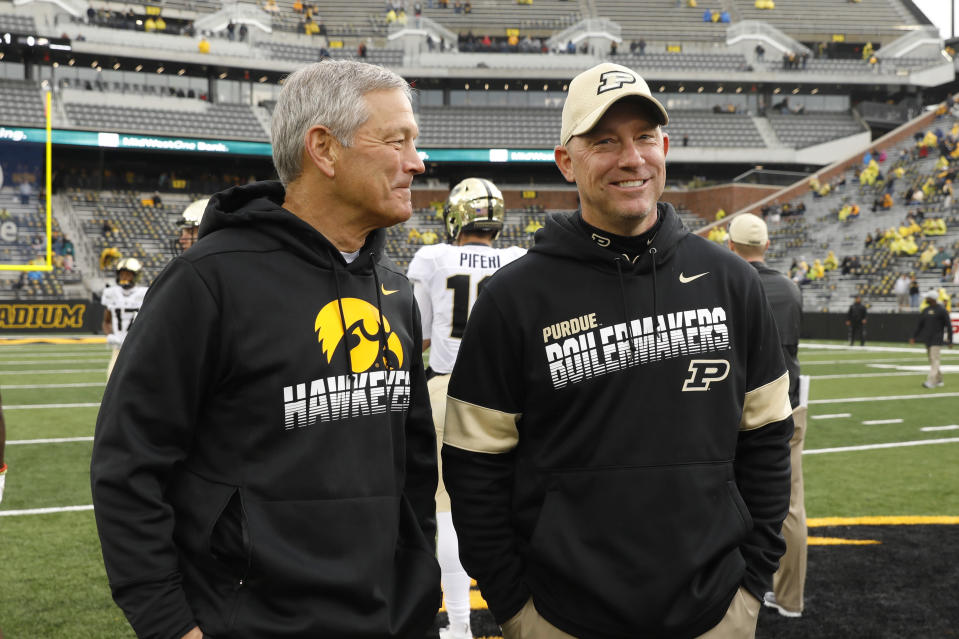 FILE - In this Oct. 19, 2019, file photo, Iowa head coach Kirk Ferentz talks with Purdue head coach Jeff Brohm, right, before an NCAA college football game in Iowa City, Iowa. Purdue offensive coordinator Brian Brohm went through his usual practice routine this week. He met with his older brother, Jeff, about game planning and the initial play-calling script as he prepared for Saturday's long-awaited season opener against Iowa. Less than a week after the Boilermakers fourth-year head coach tested positive for COVID-19 and was forced into isolation for 10 days, it's the other Brohm taking charge this weekend.(AP Photo/Charlie Neibergall, FIle)