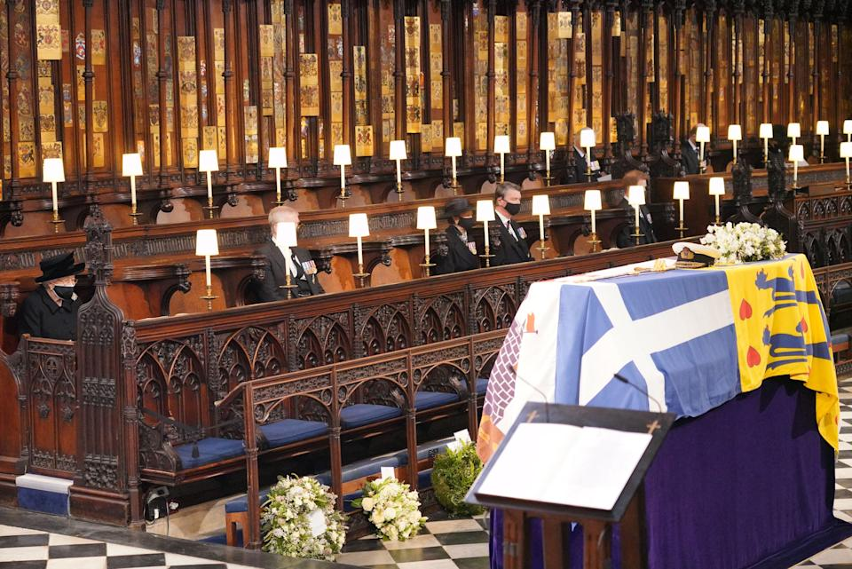 TOPSHOT - Queen Elizabeth II looks at the coffin of Britain's Prince Philip, Duke of Edinburgh during his funeral service at St George's Chapel in Windsor Castle in Windsor, west of London, on April 17, 2021. - Philip, who was married to Queen Elizabeth II for 73 years, died on April 9 aged 99 just weeks after a month-long stay in hospital for treatment to a heart condition and an infection. (Photo by Jonathan Brady / POOL / AFP) (Photo by JONATHAN BRADY/POOL/AFP via Getty Images)