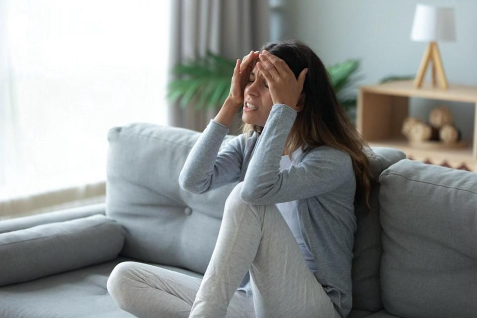 Stressed unhappy woman touching forehead, suffering from strong headache or chronic migraine
