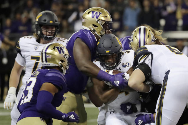 California running back Christopher Brown Jr., second from right, is tackled as he carries the ball against Washington during the first half of an NCAA college football game Saturday, Sept. 7, 2019, in Seattle. (AP Photo/Ted S. Warren)