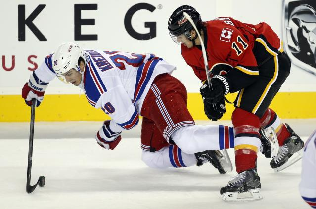 New York Rangers' Chris Kreider, left, gets knocked to the ice by Calgary Flames' Mikael Backlund, from Sweden, during the first period of an NHL hockey preseason game Monday, Sept. 23, 2013, in Calgary, Alberta. (AP Photo/The Canadian Press, Jeff McIntosh)