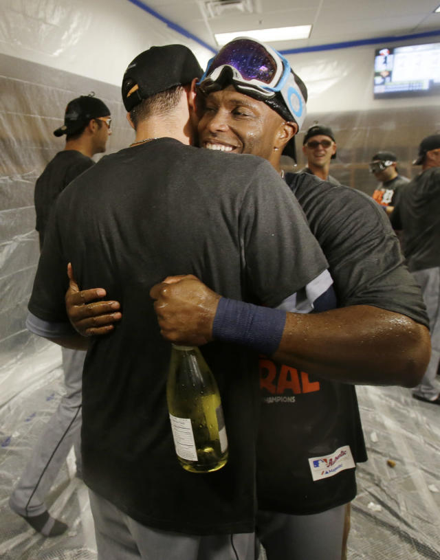 Detroit Tigers' Torii Hunter, right, and a teammate hug as players celebrate after the Tigers clinched the AL Central title with a 1-0 win over the Minnesota Twins in a baseball game, Wednesday, Sept. 25, 2013, in Minneapolis.Hunter drove in the run with a single in the first inning. (AP Photo/Jim Mone)