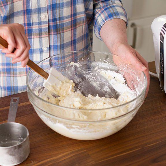 Person using a spatula to wipe the excess frosting from the sides of their glass bowl