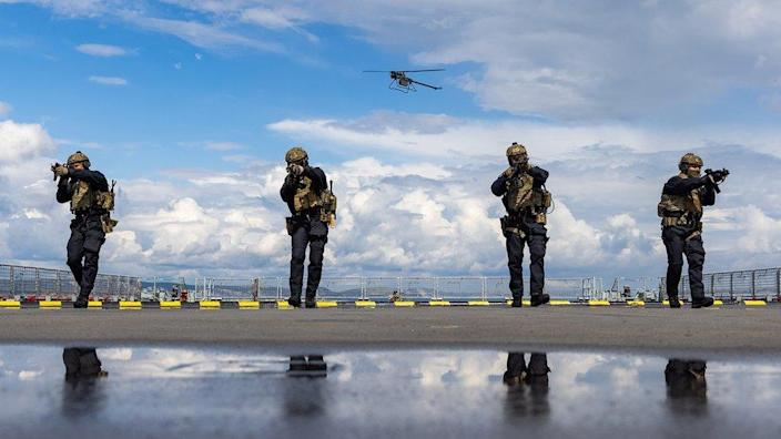 Four marines take combat stances with a drone flying overhead