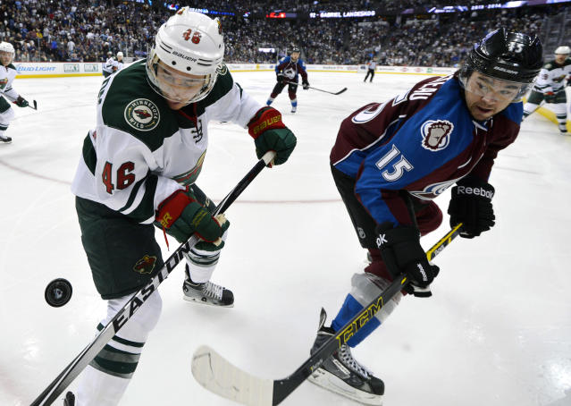 Minnesota Wild defenseman Jared Spurgeon (46) and Colorado Avalanche right wing P.A. Parenteau (15) eye the puck in the second period of Game 2 of an NHL hockey first-round playoff series on Saturday, April 19, 2014, in Denver. (AP Photo/Jack Dempsey)
