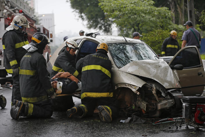 In this Nov. 25, 2012 photo, firefighters rescue a man from a car crash in Sao Paulo, Brazil. Three men were injured when they lost control of their Ford Ka car on one of Sao Paulo main avenues during a rainy morning. Brazilian drivers are dying at far higher rates than those in richer nations and safety experts say it's in part because they're riding in cars made with hardly any safety features. An AP analysis of data from Brazil's Health Ministry found that drivers and occupants die at rate nearly four times that of the United States. (AP Photo/Victor R. Caivano)