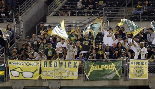 Fans cheer on the Oakland Athletics from the outfield seat during the sixth inning of a baseball game against the Los Angeles Angels on Tuesday, April 30, 2013 in Oakland. Calif. (AP Photo/Marcio Jose Sanchez)