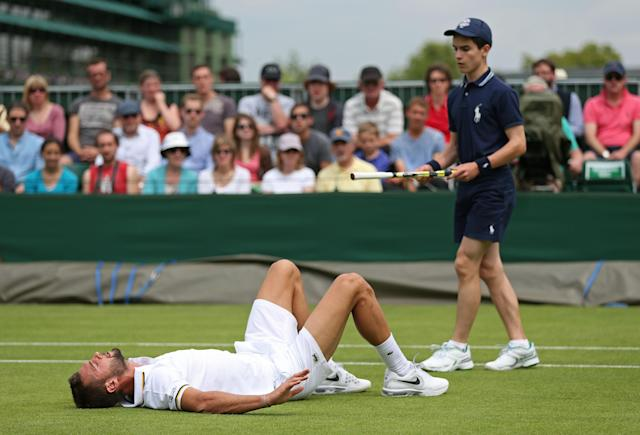 LONDON, ENGLAND - JUNE 26: Benoit Paire of France lies on the grass as a ballboy hands his racquet back to him during his Gentlemen's Singles second round match against Stephane Robert of France on day three of the Wimbledon Lawn Tennis Championships at the All England Lawn Tennis and Croquet Club on June 26, 2013 in London, England. (Photo by Clive Brunskill/Getty Images)
