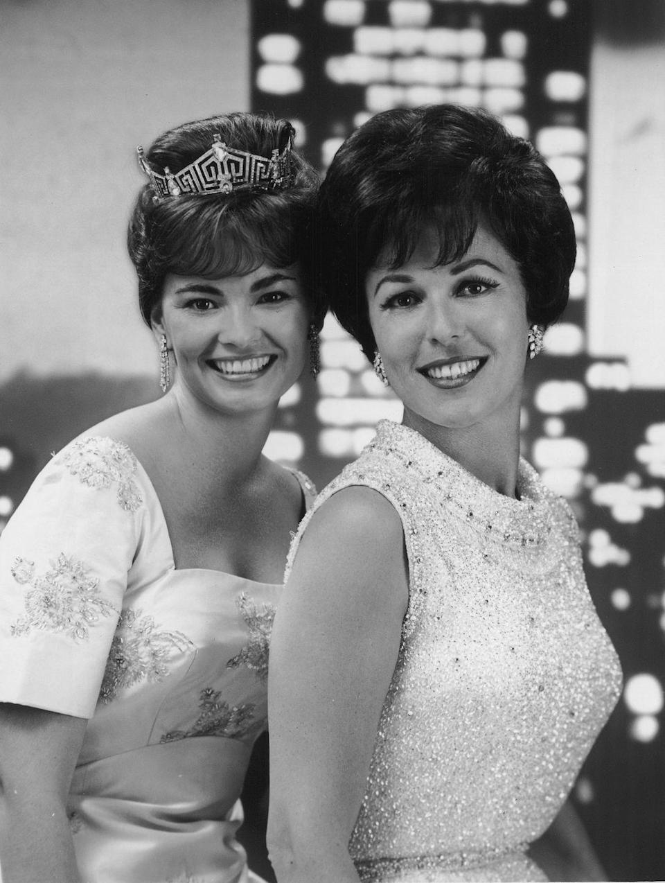 <p>Former Miss Americas, Vonda Kay Van Dyke (1965) and Bess Myerson (1945), strike a pose in embroidered evening gowns, while attending the 1966 Miss America pageant. </p>