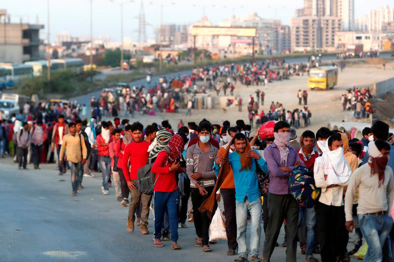 Migrant workers walk towards a bus station along a highway with their families as they return to their villages, during a 21-day nationwide lockdown to limit the spreading of coronavirus disease (COVID-19), in Ghaziabad