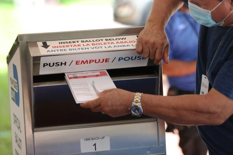 A poll worker places vote-by-mail ballots into a ballot box at the Miami-Dade Election Department headquarters on October 14, 2020
