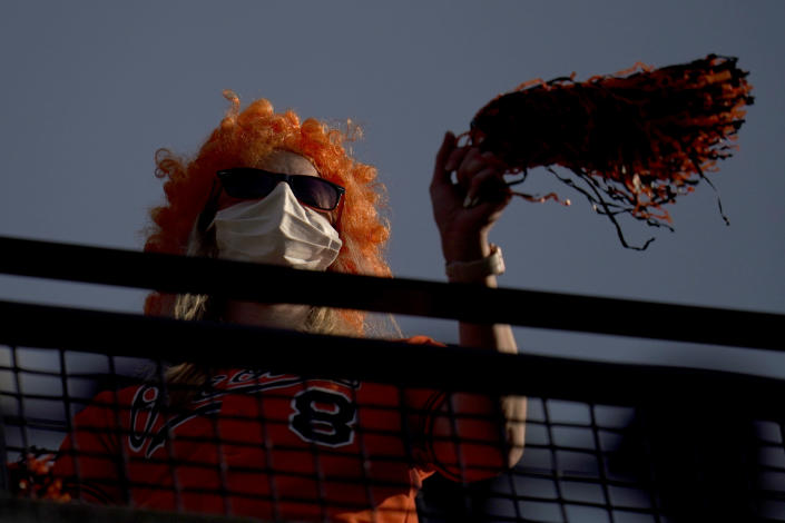 A fan waves pompons during the sixth inning of a baseball game between the Baltimore Orioles and the Boston Red Sox, Thursday, April 8, 2021, on Opening Day in Baltimore. (AP Photo/Julio Cortez)