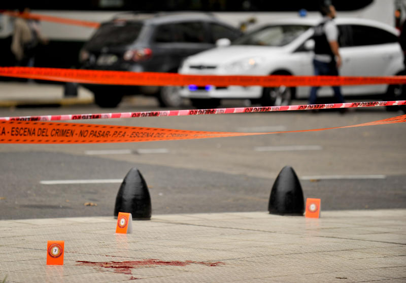 Evidence tent markers dot the crime scene where lawmaker Hector Olivares was seriously injured and another man was killed after they were shot at from a parked car near Congress in Buenos Aires, Argentina, Thursday, May 9, 2019. The lawmaker was seriously injured while provincial official Miguel Marcelo Yadón was killed, in one of the most brazen political attacks in the South American country since it returned to democracy in 1983. (AP Photo/Natacha Pisarenko)