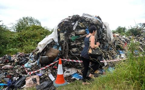 Local residents walk past the huge pile of rubbish - Credit: Dan Rowlands / SWNS