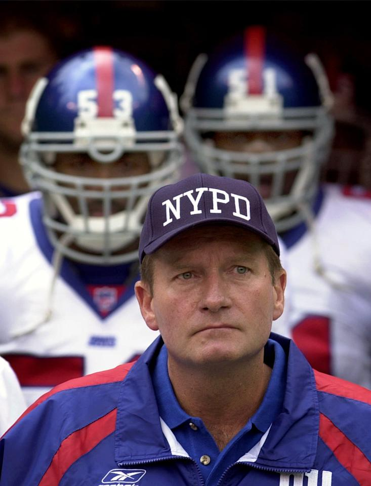 New York Giants coach Jim Fassel wears a New York Police Department cap while pausing during a moment of silence before a game against the Kansas City Chiefs at Arrowhead Stadium in Kansas City, Mo., Sunday, Sept. 23, 2001. New York coaches and officials wore New York emergency services caps to honor those killed at the World Trade Center during the Sept. 11 terrorist attacks. (AP Photo/Charlie Riedel)