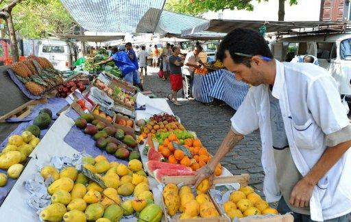 "This file photo shows a vendor arranging fruits at a market in Rio de Janeiro, in 2011. Brazil's Central Bank governor on Monday expressed confidence that the country is ""on track to continue the convergence toward the center of the inflation target"" of around 4.5 percent, despite a spike in consumer prices, particularly food prices, in mid-July"