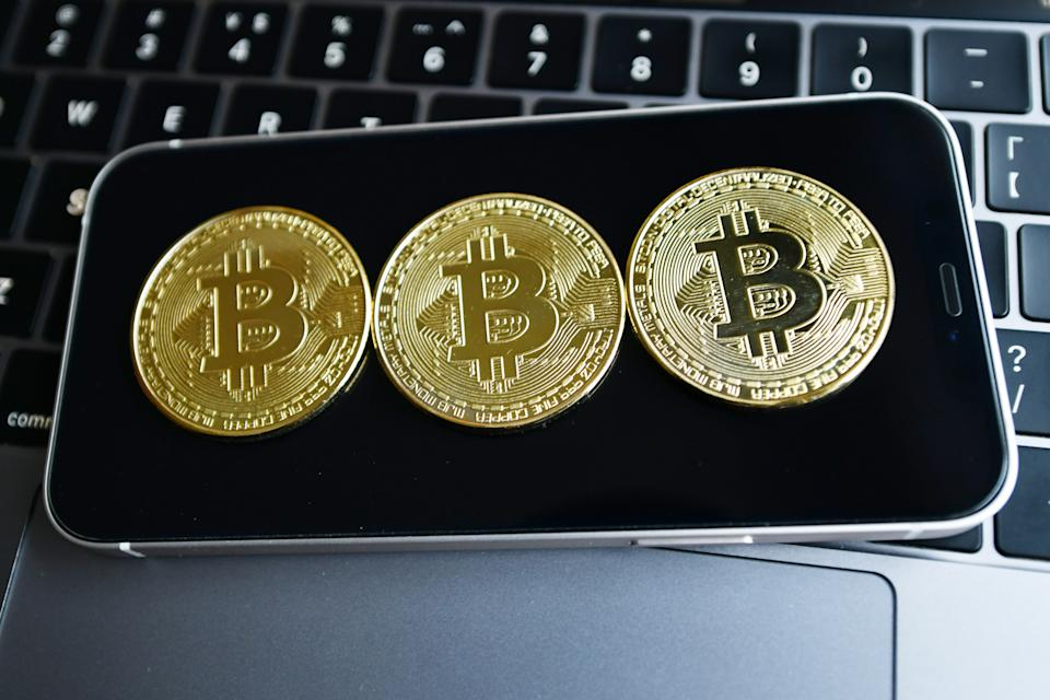 CHINA - 2021/02/26: In this photo illustration, Bitcoins seen displayed on top of a smartphone. (Photo Illustration by Sheldon Cooper/SOPA Images/LightRocket via Getty Images)