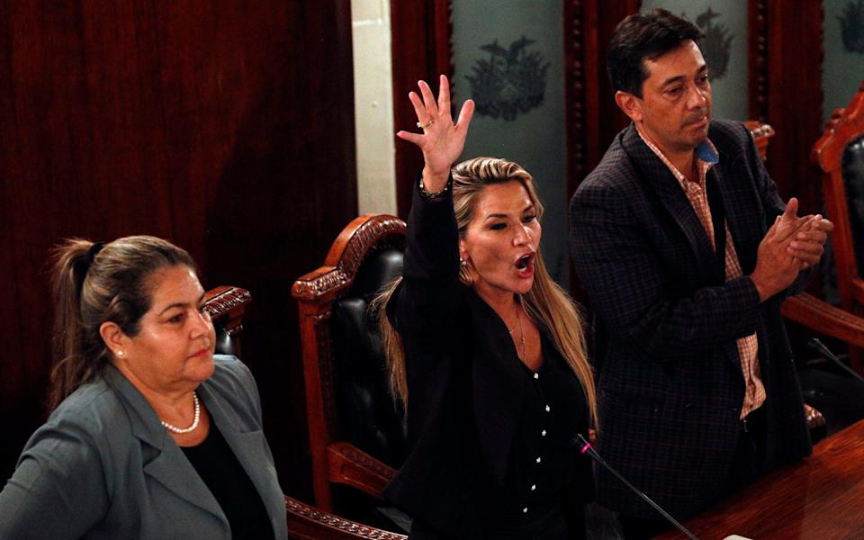 Deputy speaker Jeanine Anez, centre, assumes the presidency in La Paz on Tuesday - AP