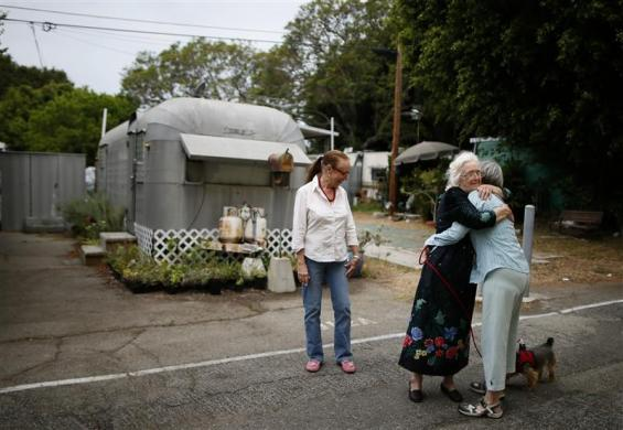 Mary Herring (C), 78, hugs a neighbor as Gayle Cooper (L), 66, looks on in Village Trailer Park in Santa Monica, July 12, 2012.