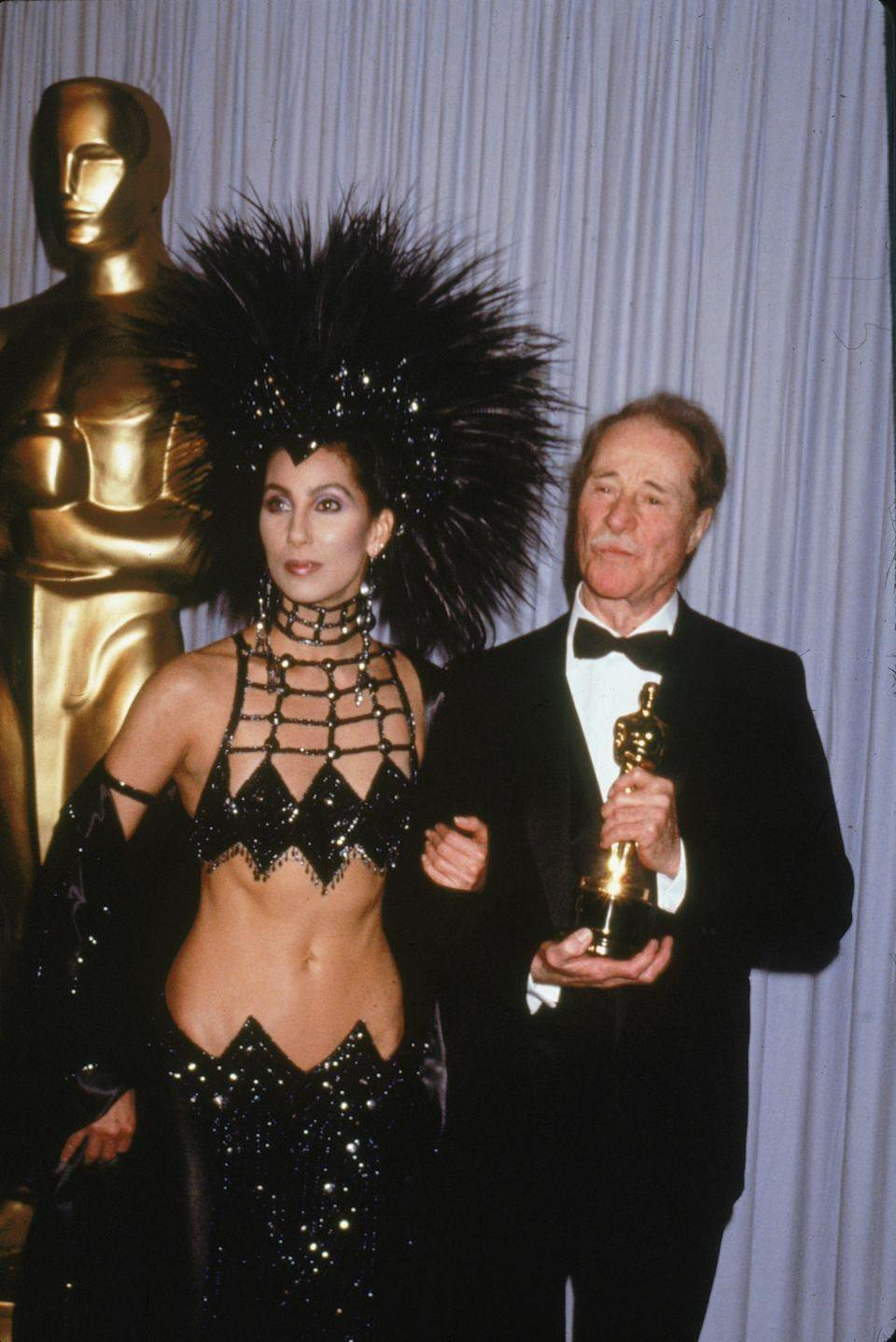 """<p>Even if she hadn't won the Oscar for her role in <em><a href=""""https://www.amazon.com/Moonstruck-Cher/dp/B07JCGMLMD/ref=sr_1_1?s=instant-video&ie=UTF8&qid=1547582767&sr=1-1&keywords=Moonstruck&tag=syn-yahoo-20&ascsubtag=%5Bartid%7C10055.g.5148%5Bsrc%7Cyahoo-us"""" rel=""""nofollow noopener"""" target=""""_blank"""" data-ylk=""""slk:Moonstruck"""" class=""""link rapid-noclick-resp"""">Moonstruck</a></em><span class=""""redactor-invisible-space"""">, <a href=""""http://oscar.go.com/photos/2017/unforgettable-fashion-moments/cher-1986"""" rel=""""nofollow noopener"""" target=""""_blank"""" data-ylk=""""slk:Cher still would've stolen the show"""" class=""""link rapid-noclick-resp"""">Cher still would've stolen the show</a> in this <a href=""""https://www.goodhousekeeping.com/beauty/fashion/g4208/oscars-red-carpet-fashion-fails/"""" rel=""""nofollow noopener"""" target=""""_blank"""" data-ylk=""""slk:custom Bob Mackie dress"""" class=""""link rapid-noclick-resp"""">custom Bob Mackie dress</a>. Of course, she topped it with a huge feathered headdress. But believe it or not, it wasn't even the most revealing outfit at the 1986 Oscars ... </span></p><p><span class=""""redactor-invisible-space""""><strong>RELATED:</strong> <a href=""""https://www.goodhousekeeping.com/health/diet-nutrition/a44341/what-cher-eats-in-a-day/"""" rel=""""nofollow noopener"""" target=""""_blank"""" data-ylk=""""slk:What Cher Eats in a Day to Look So Fit"""" class=""""link rapid-noclick-resp"""">What Cher Eats in a Day to Look So Fit</a><br></span></p>"""