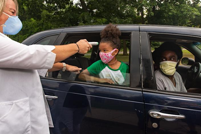 Nurse Sarah Ladd takes 5-year-old Nova Wright's temperature as she's dropped off at school | Gillian Laub for TIME