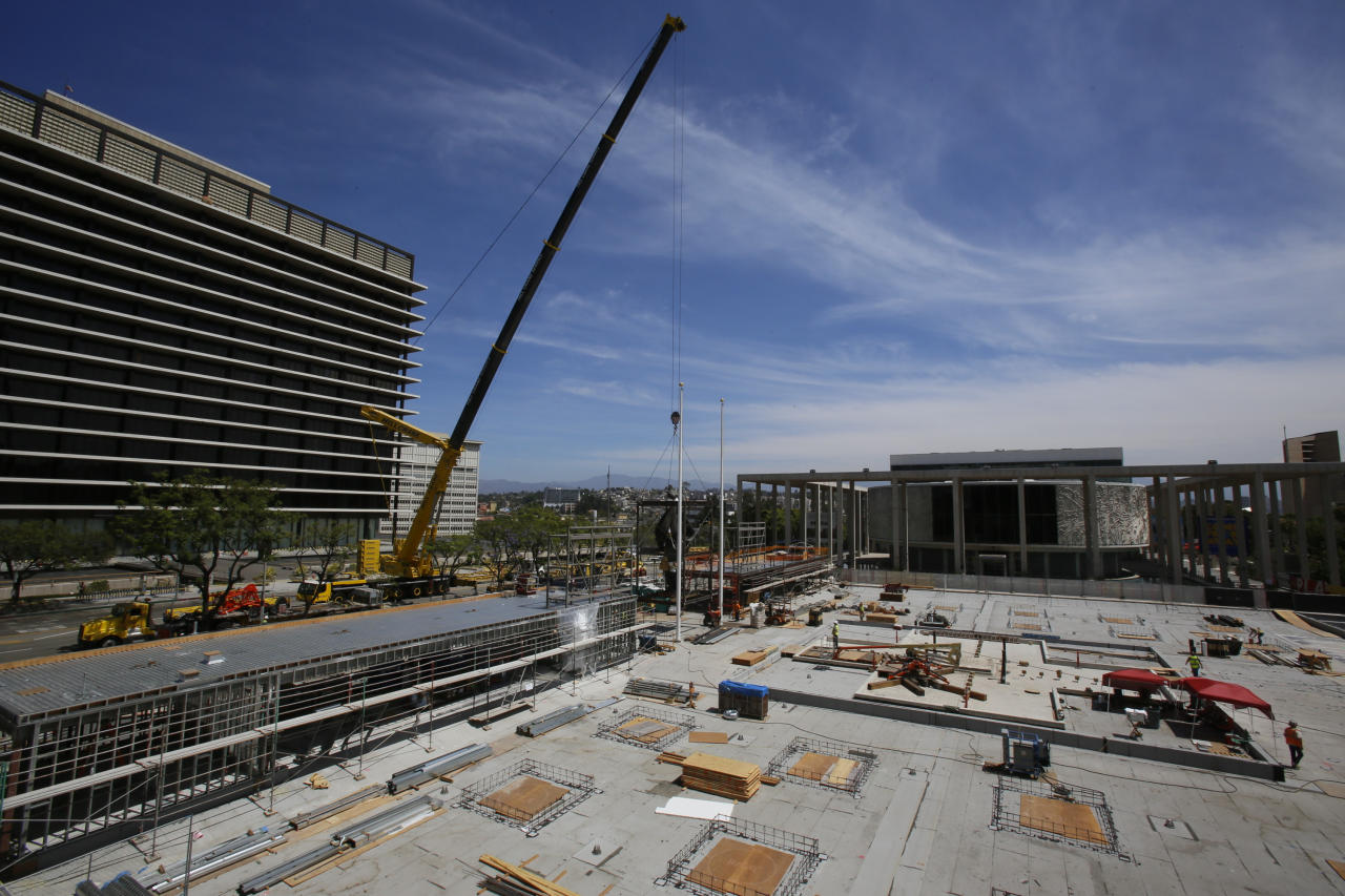 """The Music Center Plaza's Jacques Lipchitz sculpture, """"Peace on Earth,"""" a 10-ton bronze sculpture is hoisted by a crane to its new home on the west side of Music Center Plaza closer to the Joe Ferraro building, seen left , downtown Los Angeles Saturday, July 21, 2018. (AP Photo/Damian Dovarganes)"""