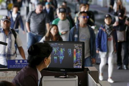 Passengers wearing masks to prevent contracting Middle East Respiratory Syndrome (MERS) walk past a thermal imaging camera at Incheon International Airport in Incheon