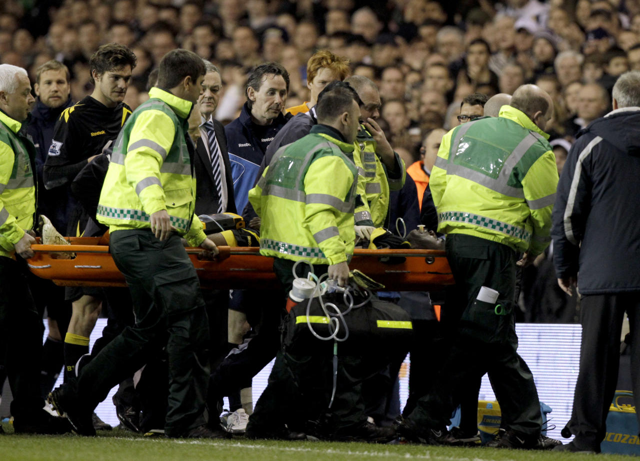 Bolton Wanderers' Fabrice Muamba is stretchered off the pitch after collapsing during the English FA Cup quarterfinal soccer match between Tottenham Hotspur and Bolton Wanderers at White Hart Lane stadium in London, Saturday, March 17, 2012. Bolton midfielder Fabrice Muamba has been carried off the field at Tottenham after medics appeared to be trying to resuscitate him during an FA Cup quarterfinal that was abandoned. Muamba went to the ground in the 41st minute with no players around him and the game was immediately stopped. (AP Photo/Matt Dunham)