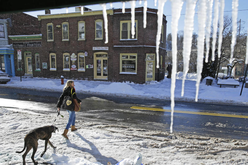 A women walks with her dog past icicles hanging from a store awning Wednesday, Jan. 22, 2014, in Philadelphia. A winter storm stretched from Kentucky to New England and hit hardest along the heavily populated Interstate 95 corridor between Philadelphia and Boston. (AP Photo/Matt Rourke)