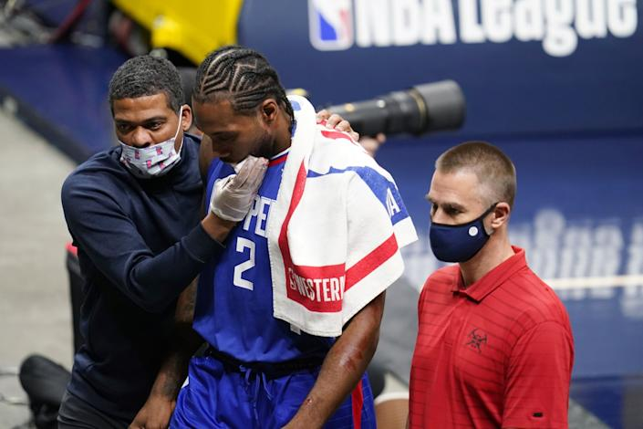 Clippers forward Kawhi Leonard is accompanied by two men off the court.