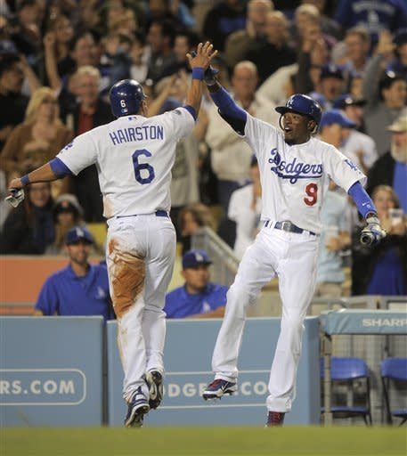 Los Angeles Dodgers' Jerry Hairston Jr., left, is congratulated by teammate Dee Gordon after scoring on a single by A.J. Ellis during the seventh inning of their baseball game against the Washington Nationals, Saturday, April 28, 2012, in Los Angeles. (AP Photo/Mark J. Terrill)