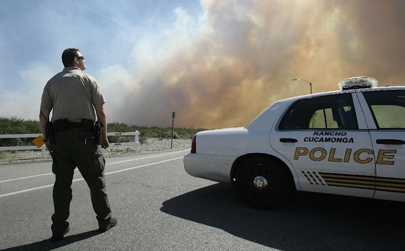 A San Bernardino Sheriff's deputy keeps an eye on a brush fire burning in Day Creek near the Etiwanda Perserve in Rancho Cucamonga, Calif., on Wednesday, April 30, 2014. Fire officials say winds gusting to 60 mph are pushing the flames through the foothills of the San Bernardino Mountains east of Los Angeles, although no homes are in immediate danger. Several neighborhoods and at least seven schools in Rancho Cucamonga have been evacuated. There's no word on what sparked the blaze but it comes in the midst of a heat wave that's created extreme fire danger. (AP Photo/The Press-Enterprise, Stan Lim) MAGS OUT; MANDATORY CREDIT