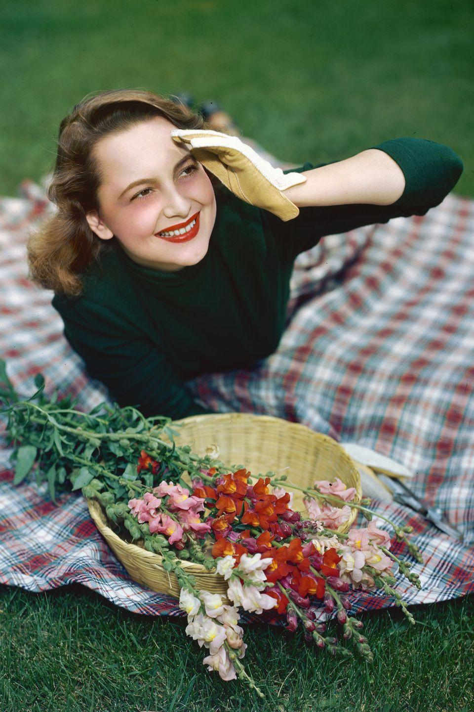 <p>Enjoying picnic weather in a green sweater and gloves atop a tartan blanket. </p>