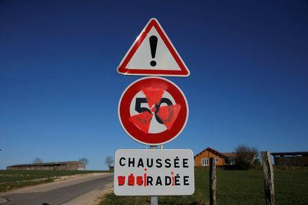 """A nuclear warning symbol and the word """"irradiated"""" are painted on road signs in the village of Bure, France, April 6, 2018. Picture taken April 6, 2018. REUTERS/Vincent Kessler"""