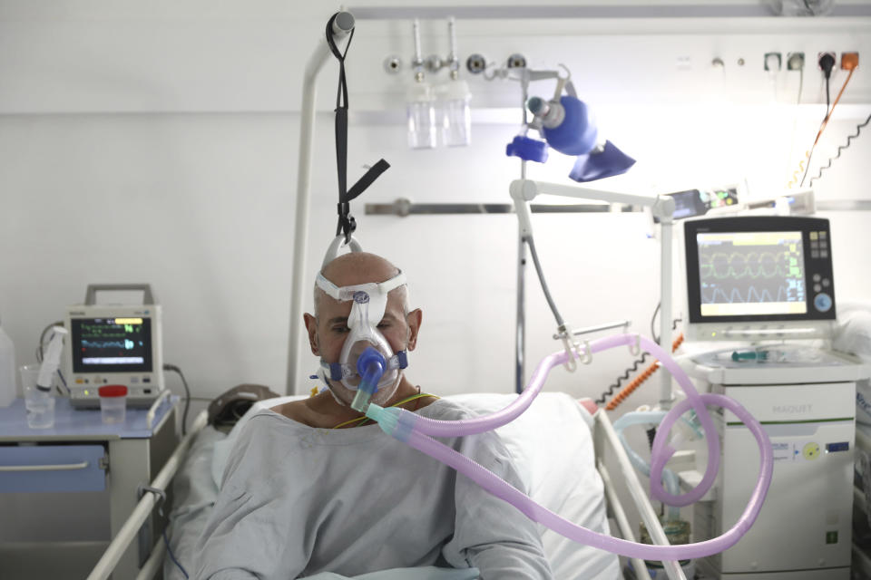 A patient breathes through an oxygen mask at the COVID-19 ICU unit of the Dr. Abdulah Nakas General Hospital in Sarajevo, Bosnia, Friday, Sept. 17, 2021. The COVID-19 rate of infections in Bosnia, a country where only about 12% of the population is fully vaccinated against COVID-19, is on the rise, authorities reported on Friday, with more than 900 new infections and 30 fatalities over the past 24 hours. (AP Photo)