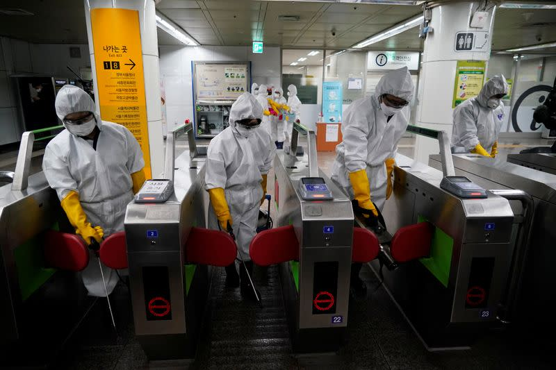 Employees from a disinfection service company sanitize a subway station in Seoul