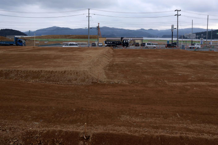 In this March 5, 2016, file photo, trucks and cars pass through the leveled city of Minamisanriku, Miyagi Prefecture, northern Japan, nearly five years after the Tsunami. (AP Photo/Eugene Hoshiko, File)