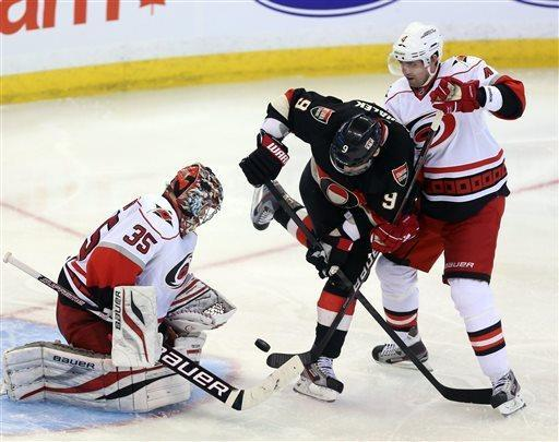 Ottawa Senators' Milan Michalek (9) is checked by Carolina Hurricanes' Jamie McBain (4) as goaltender Justin Peters (35) watches the puck during the third period of their NHL hockey game in Ottawa, Ontario, Tuesday, April 16, 2013. The Senators won 3-2. (AP Photo/The Canadian Press, Fred Chartrand)