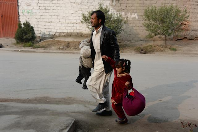 <p>An Afghan man runs with two children near an office of the British charity Save the Children during an ongoing attack in Jalalabad on Jan. 24, 2018. (Photo: Noorullah Shirzada/AFP/Getty Images) </p>