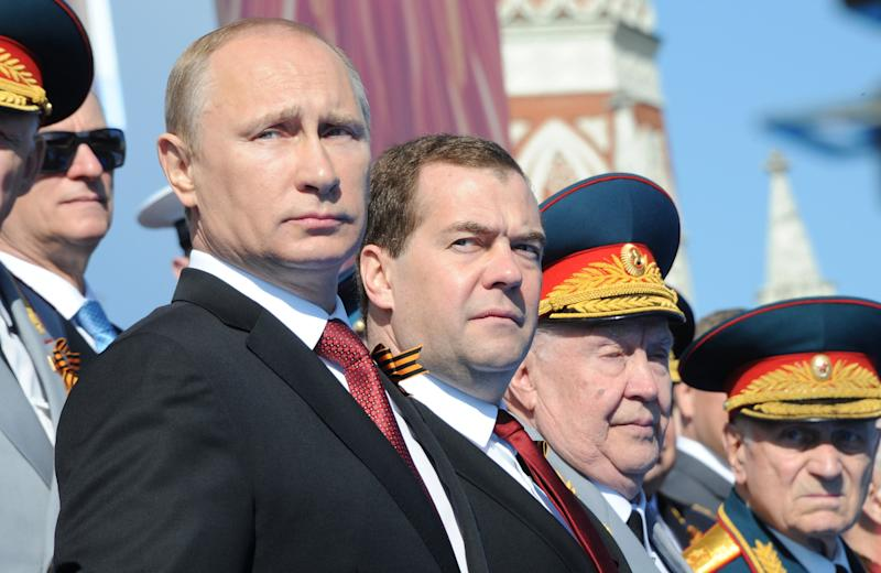 Russia's President Vladimir Putin (L) and Prime Minister Dmitry Medvedev (2nd L) attend a Victory Day parade at the Red Square in Moscow, on May 9, 2014