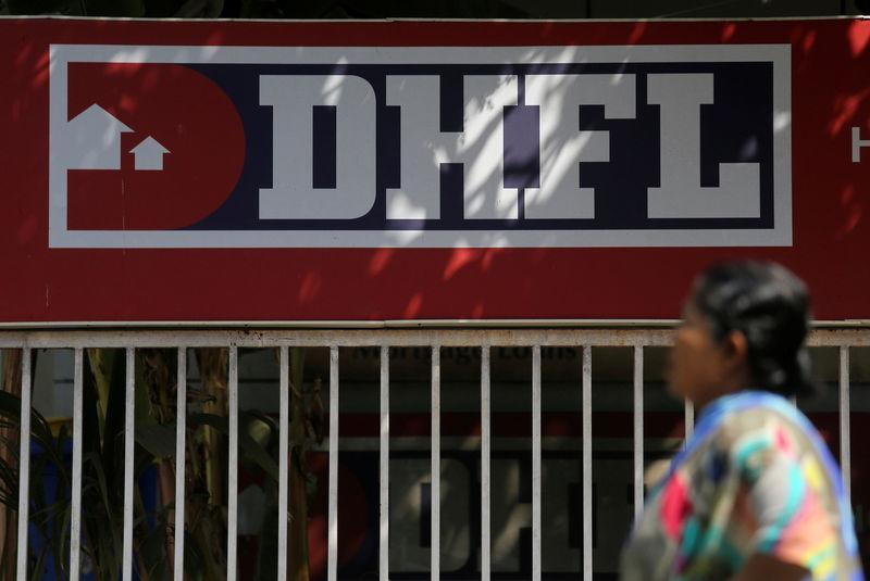 A woman walks past a signboard of Dewan Housing Finance Corporation Ltd. (DHFL) outside its office on the outskirts of Mumbai