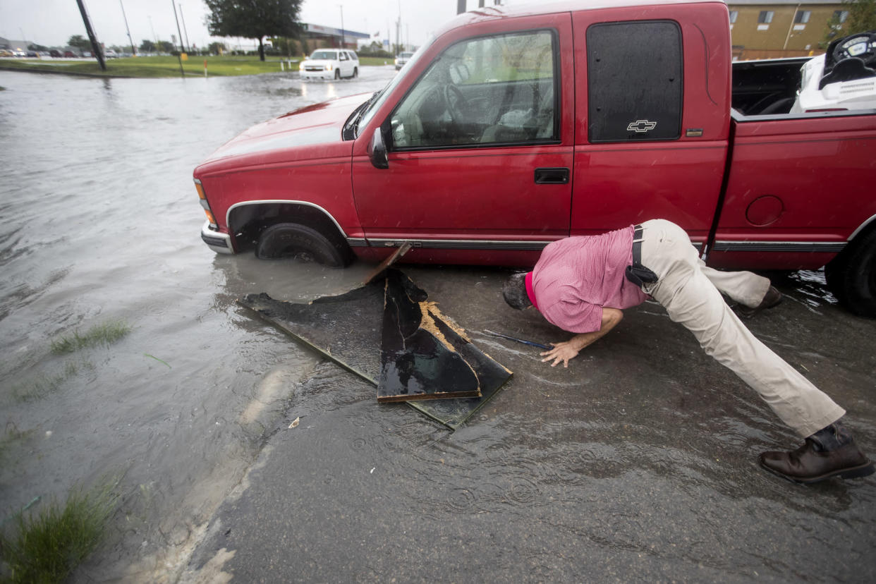 Felipe Morales works on getting his truck out of a ditch filled with high water during a rain storm stemming from rain bands spawned by Tropical Storm Imelda on Sept. 17, 2019, in Houston. (Photo: Brett Coomer/Houston Chronicle via AP)