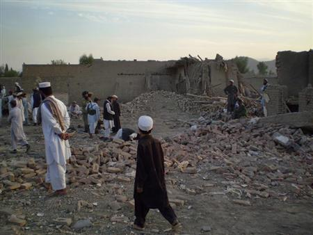 Tribesmen gather at a damaged house after a missile struck in Dandi Darpakheil village on the outskirts of Miranshah