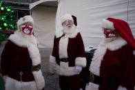 Santa Claus' from left, Larry Hansen, Charlie Bush and Bill Sandeen, wear masks as a precaution against coronavirus while waiting before the opening of a Santa drive-thru selfie station at Glittering Lights, a drive-thru holiday lights display, Thursday, Dec. 10, 2020, in Las Vegas. Santa behind plexiglass. Santa in a life-sized snow globe. Santa wearing a face mask. And, of course, Zoom Santa. In this socially distant holiday season, Santa Claus is still coming to towns (and shopping malls) across America but with a few 2020 rules in effect. (AP Photo/John Locher)