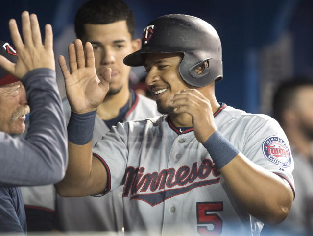 Minnesota Twins' Eduardo Escobar celebrates in the dugout after scoring on a Robbie Grossman double in the sixth inning of their baseball game against the Toronto Blue Jays in Toronto on Tuesday July 24, 2018. (Fred Thornhill/The Canadian Press via AP)